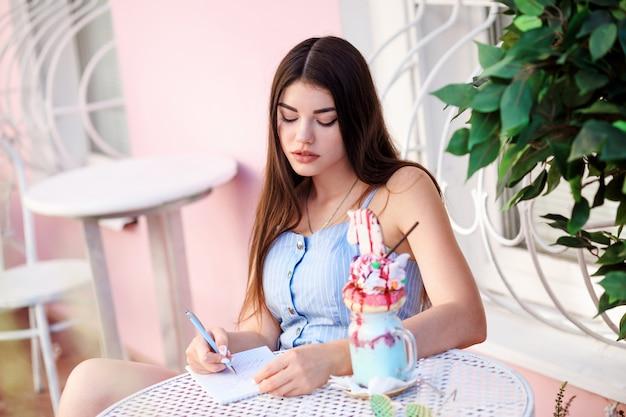 Linda mulher morena está escrevendo em seus laticínios enquanto está sentado à mesa no café ao ar livre.