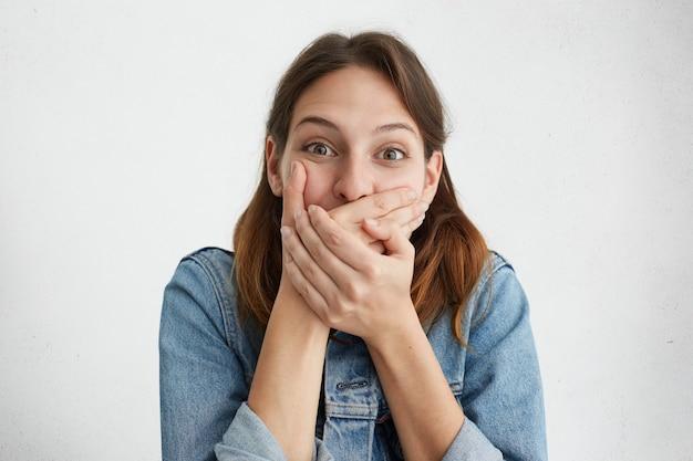 Linda mulher morena explodindo de rir cobrindo a boca