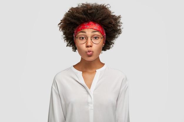 Linda mulher morena faz beicinho, tem corte de cabelo afro, faz careta, usa óculos redondos, bandana vermelha e camisa branca, fica encostada na parede. conceito de expressões faciais