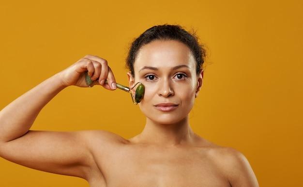 Linda mulher morena fazendo massagem facial com rolo de jade isolado em backgroung amarelo