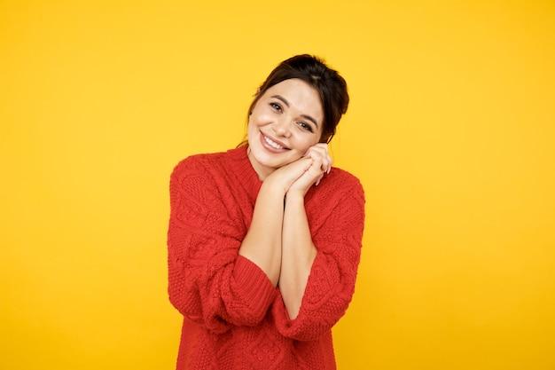 Linda mulher morena feliz em clothers vermelhos no estúdio amarelo.