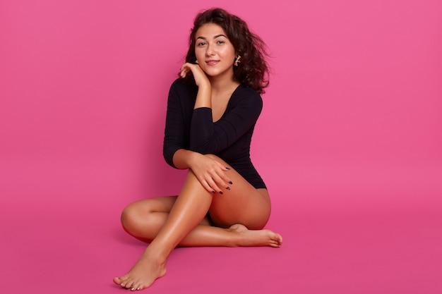 Linda mulher morena. garota com corpo perfeito, sentada no chão no estúdio isolado sobre parede rosa, bela dama com cabelos ondulados e pernas longas, pele limpa e macia. aparência romântica delicada