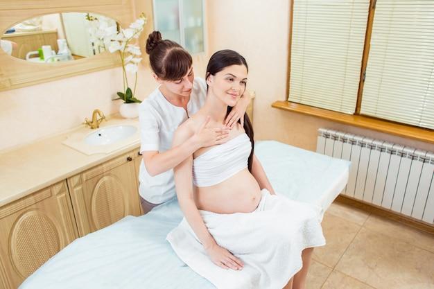Linda mulher morena grávida com cabelos longos, desfruta de uma massagem nos ombros e esterno em uma sala de cosmetologia