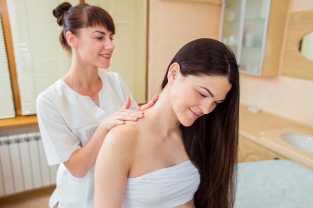 Linda mulher morena grávida com cabelos longos, desfrutando de massagem nos ombros e costas em uma sala de beleza