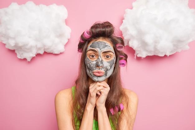 Linda mulher morena mantém as mãos embaixo do queixo e aplica rolos de cabelo para fazer máscara de argila de penteado para poses refrescantes de pele contra a parede rosa
