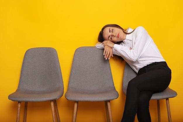 Linda mulher morena moderna e elegante está sentada na fila das cadeiras para uma entrevista de emprego