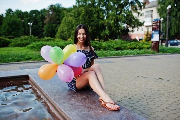 Linda mulher morena na rua da cidade com balões nas mãos.