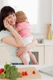 Linda mulher morena no telefone enquanto segurava seu bebê em seus braços