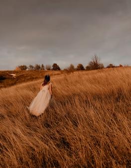Linda mulher morena noiva com vestido branco e terno está andando na grama alta no campo no verão