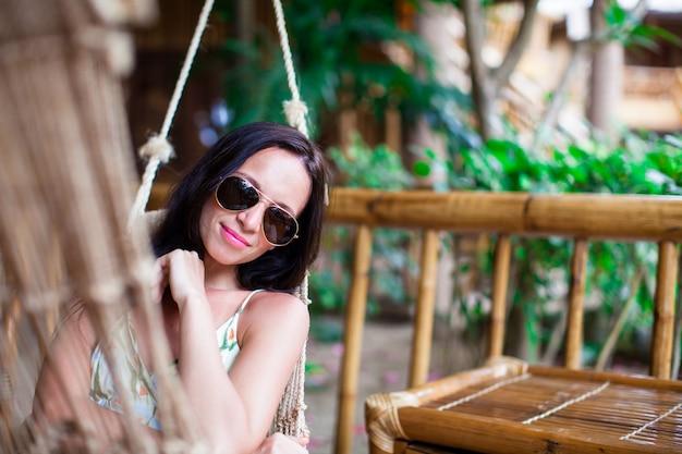 Linda mulher morena relaxante na rede no hotel de luxo exótico