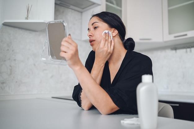 Linda mulher morena, removendo a maquiagem do rosto com espelho. menina bonito bonito beleza natural, limpeza de rosto com esponja de algodão. cosmetologia e spa, problema de cuidados com a pele, conceito de tratamento da acne