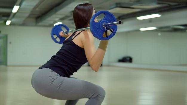 Linda mulher morena se agacha com uma barra no ginásio. conceito de fitness