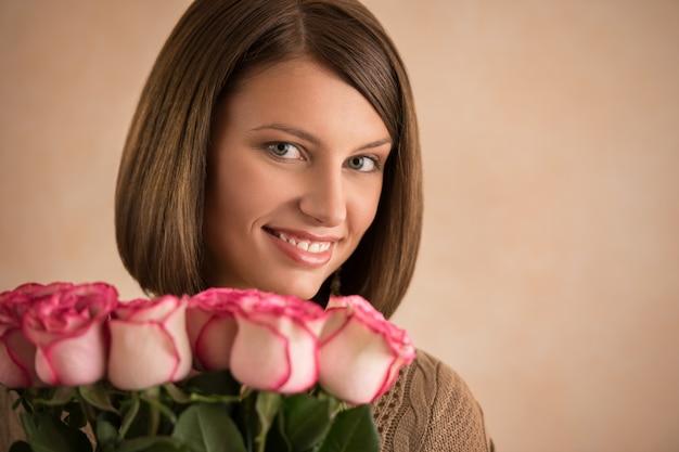 Linda mulher morena segurando cacho de rosas