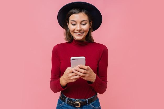 Linda mulher morena segurando um celular moderno e digitando mensagens no dispositivo smartphone