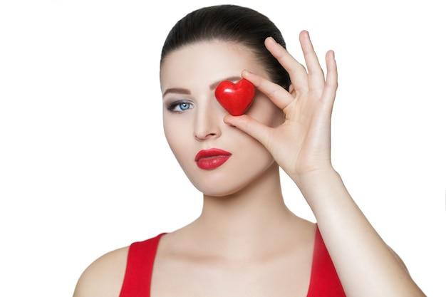 Linda mulher morena segurando um coração vermelho na frente do rosto. dia dos namorados