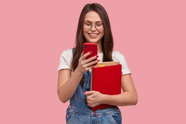 Linda mulher morena segurando um telefone celular, enviando uma mensagem de texto, feliz por ler os comentários na postagem, segurando um livro didático