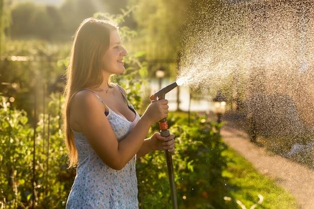 Linda mulher morena segurando um tubo de mangueira no jardim em dia de sol