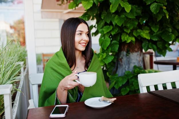 Linda mulher morena, sentada em cima da mesa no café capa xadrez com xícara de café.