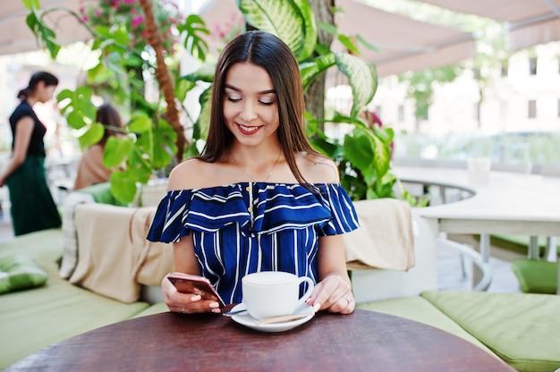 Linda mulher morena, sentada em cima da mesa no café com uma xícara de café.