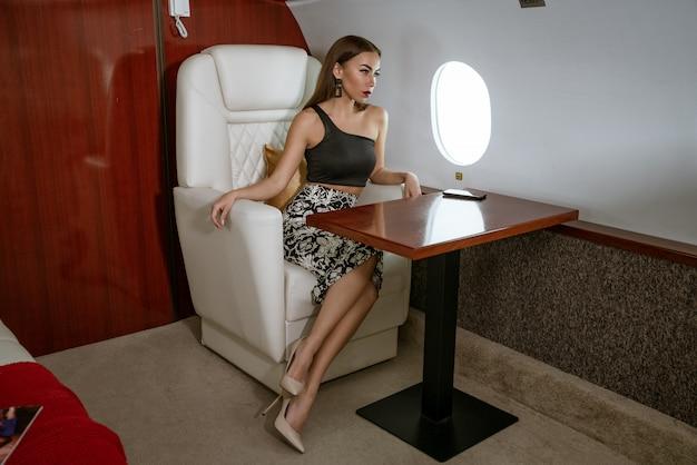 Linda mulher morena sentada em um assento de avião privado