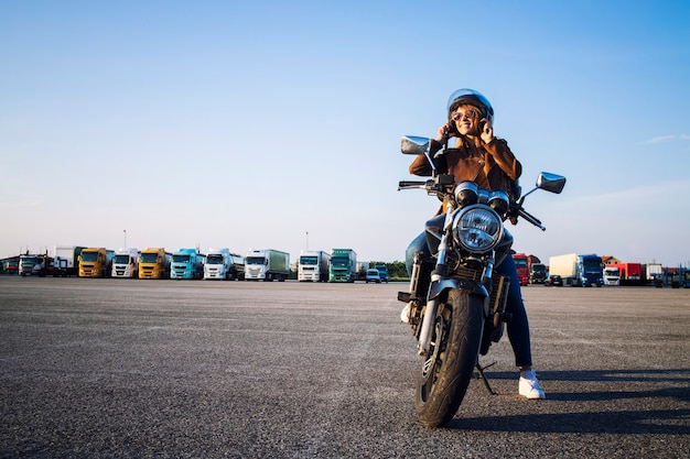 Linda mulher morena sexy em uma jaqueta de couro sentada em uma motocicleta estilo retro se preparando para o passeio