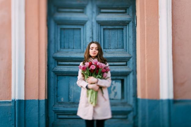 Linda mulher morena sorridente em frente a porta velha com um buquê de tulipas frescas.