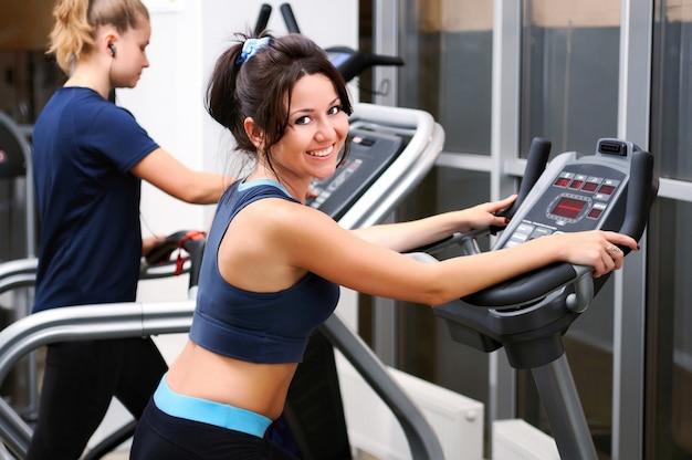 Linda mulher morena sorridente posando de treino em bicicleta ergométrica