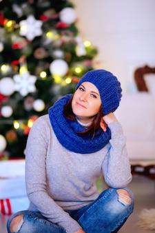Linda mulher morena sorridente, sentada no chão com roupas casuais de inverno, aproveitando as férias