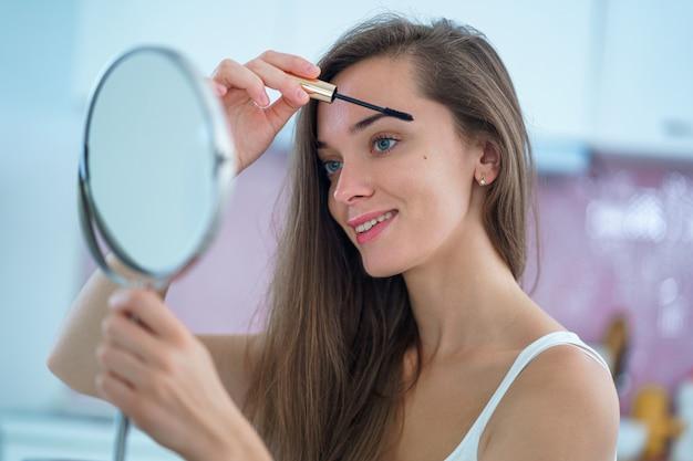 Linda mulher morena sorridente usa um pequeno espelho redondo e coloca rímel preto nos cílios durante a maquiagem em casa pela manhã