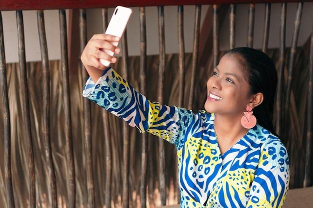 Linda mulher morena tirando uma selfie com o telefone em casa
