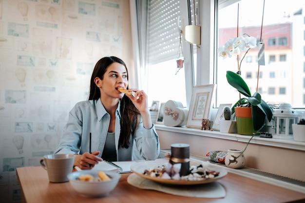 Linda mulher morena tomando café da manhã em seu apartamento.