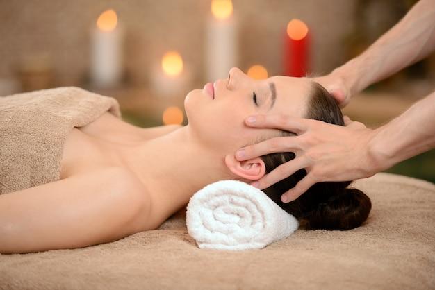 Linda mulher morena tomando massagem na cabeça.