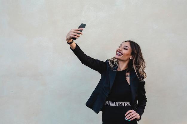 Linda mulher morena vestida de forma elegante leva uma selfie ao ar livre. mulher de negócios feliz.