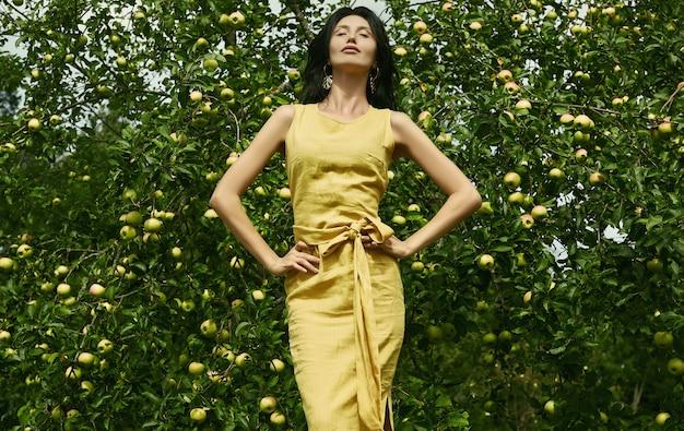 Linda mulher morena vestido amarelo moda no jardim de maçã