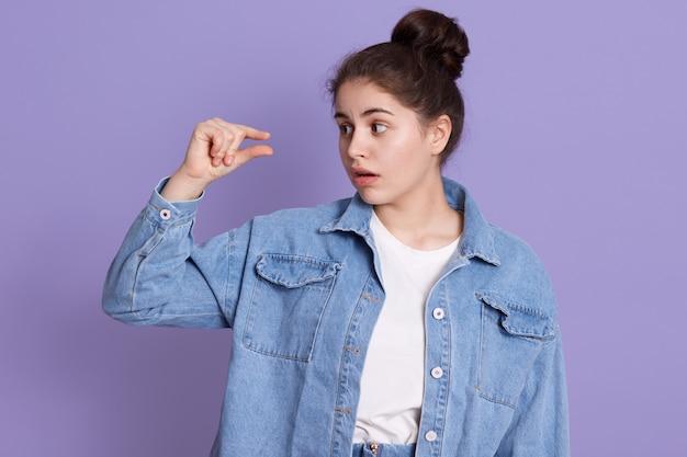 Linda mulher mostra tamanho pequeno enquanto olha para o dedo, vestindo camisa branca e jaqueta jeans, senhora morena com nó, tendo intrigado expressão facial.