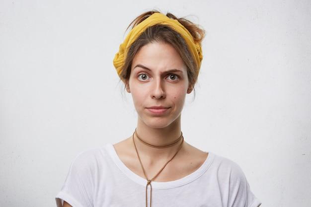 Linda mulher mostrando suspeita enquanto franzia a testa com as sobrancelhas finas. mulher jovem com aparência atraente, com dúvidas e os olhos cheios de descrença. expressões faciais