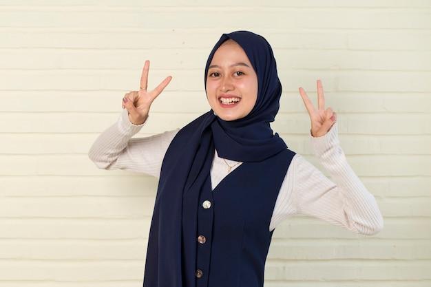 Linda mulher muçulmana asiática em hijab mostrando paz ou gesto de vitória com a mão