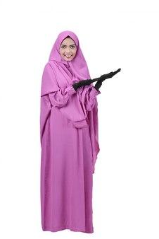 Linda mulher muçulmana asiática mostrando a área de copyspace com a mão