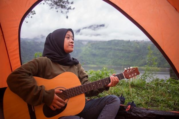 Linda mulher muçulmana asiática tocando guitarra sentada perto do lago na montanha com vista para o rio com mochila, barraca ao pôr do sol