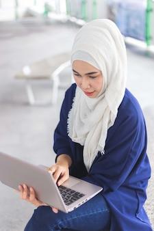 Linda mulher muçulmana asiática trabalhando com o laptop no estação de trem elétrico.