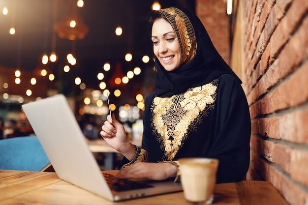 Linda mulher muçulmana com sorriso vestida com roupas tradicionais, usando o laptop para fazer compras on-line enquanto está sentado na cafeteria. na mesa de café.
