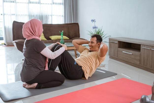Linda mulher muçulmana e marido fazendo sentar-se juntos. casal se exercitando em casa