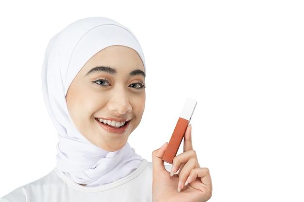 Linda mulher muçulmana em hijab sorrindo enquanto segura o frasco de batom