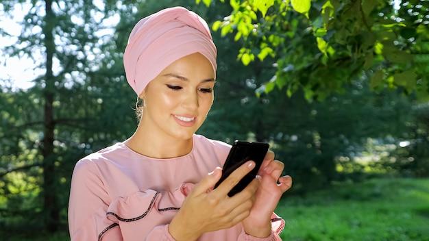 Linda mulher muçulmana no turbante com telefone no fundo das árvores.