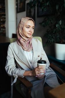 Linda mulher muçulmana parece pensativa e segura o café na mão