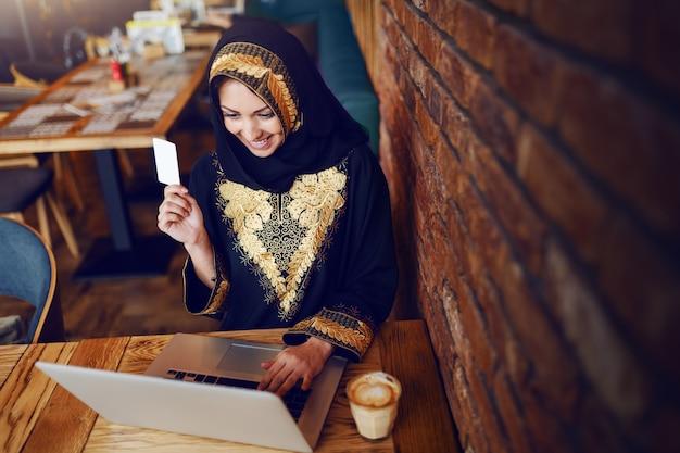 Linda mulher muçulmana sorridente, sentado no café, segurando o cartão de crédito e olhando para o laptop. na mesa de madeira são café e laptop.