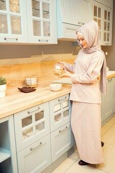 Linda mulher muçulmana usando hijab cozinhando o jantar e despejando macarrão na panela de pé sobre o fogão elétrico de perto