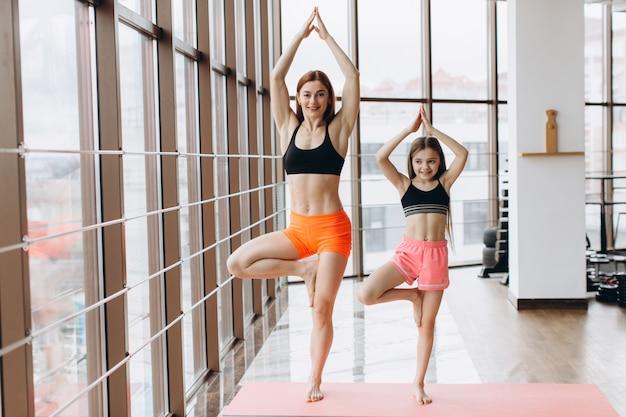 Linda mulher muscular e sua encantadora filha estão sorrindo enquanto faz ioga juntos no ginásio