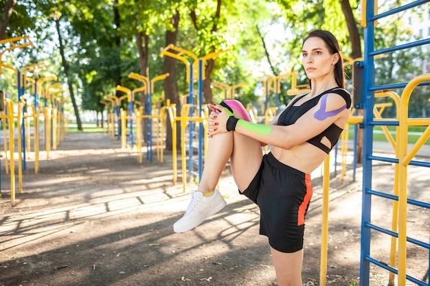 Linda mulher musculosa e flexível usando roupa esportiva preta