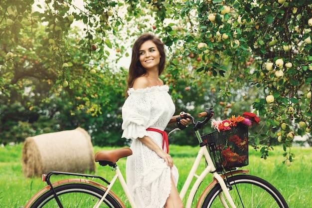 Linda mulher na bicicleta está colhendo maçãs frescas da árvore